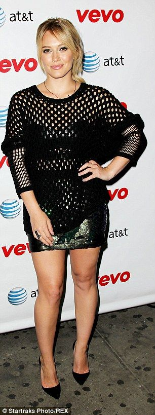 Textured frock: The star wore a black long sleeve mini dress that put on her long legs on ...