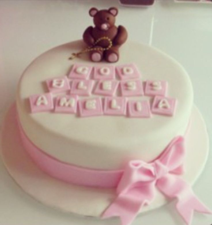 Christening cake with fondant bow and bear topper made using gum paste.