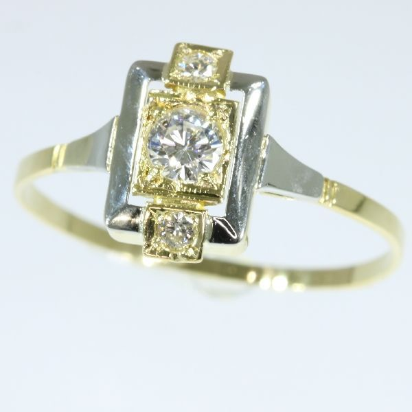 Art Deco gouden diamantring anno 1930  Soort juweel: ringConditie: zeer goed - als nieuw!Stijl: Art DecoEra: ca. 1930Materiaal: 18 K geel goud en wit goud detailsDiamant: Een briljant geslepen diamant met een geschat gewicht van  016 ct. (kleur en helderheid: G/H vs/si).Twee briljant geslepen diamanten met een geschat gewicht van  005 ct. (kleur en helderheid: G/H vs/si).Totaalgewicht van de diamant (zonder de roos geslepen diamant): ca. 021 ct. met een gemiddelde kleur en helderheid: G/H…