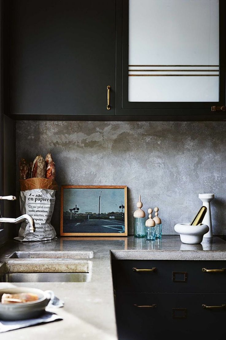 A concrete countertop and backsplash provide a lovely, textured contrast to minimally styled cabinets in this kitchen from Inside Out.