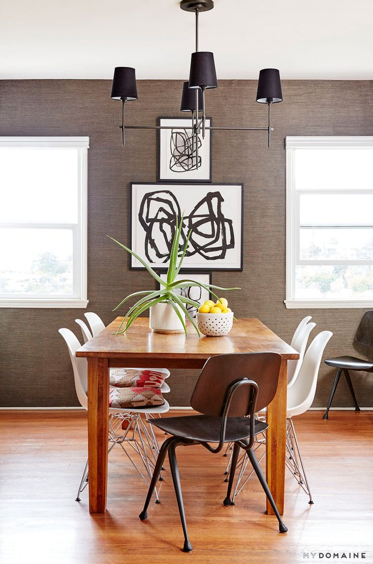 Neutral dining room with black and white art, cactus, and bowl of lemons