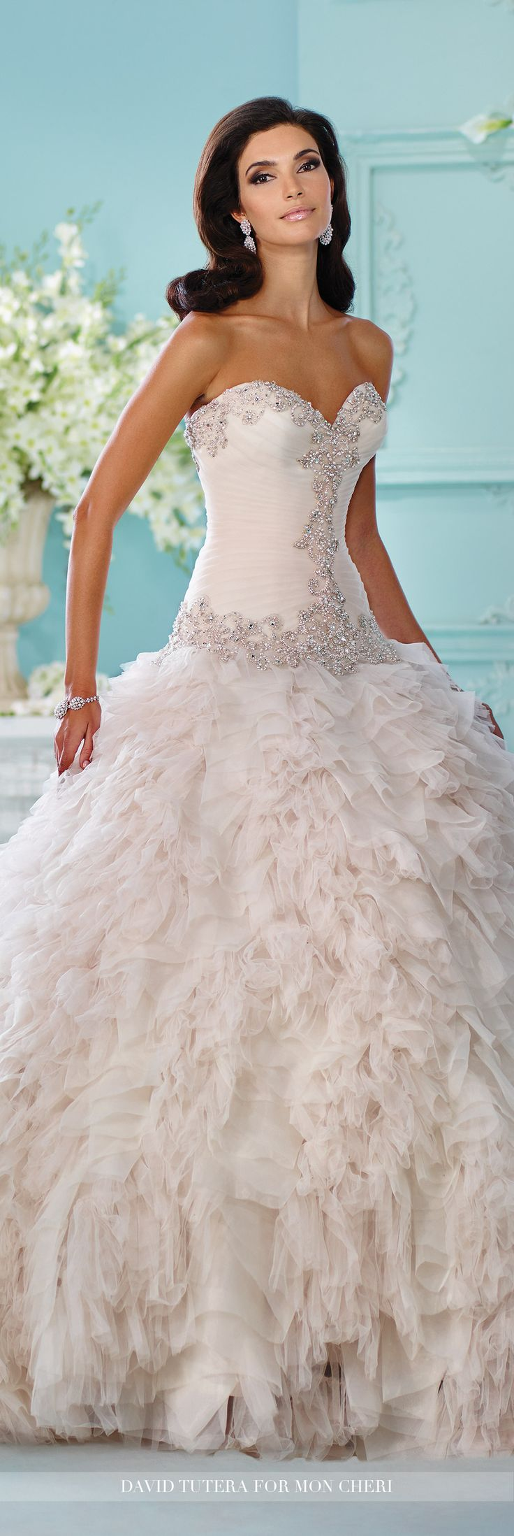 David Tutera for Mon Cheri - 216260 Meena - Strapless tulle and organza ball gown, sweetheart neckline and hand-pleated dropped waist bodice trimmed with metallic embroidery and rich jewel beaded motif, voluminous skirt with multiple layers of ruffled tulle and pleated organza, semi-cathedral length train detachable spaghetti and halter straps included.  Sizes: 0-20, 18W-26W  Pink Champagne, Ivory, White