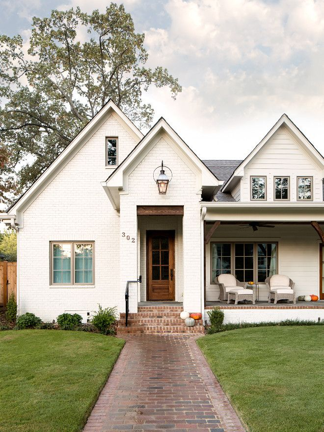White brick + wood front door + porch + cool numbers and lantern + fancy walkway