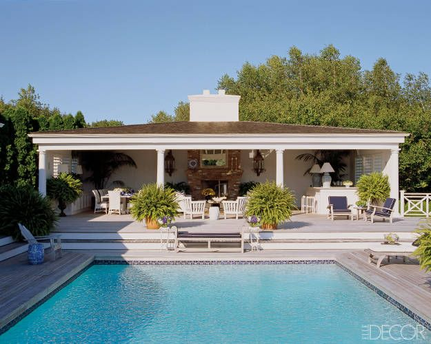 The Long Island weekend house of fashion designer Dennis Basso features a tile-bordered pool, mahogany deck, and spacious columned poolhouse with plenty of seating.