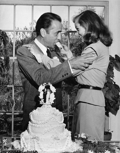 Lauren Bacall feeds Humphrey Bogart a slice of cake at their wedding, 1945.