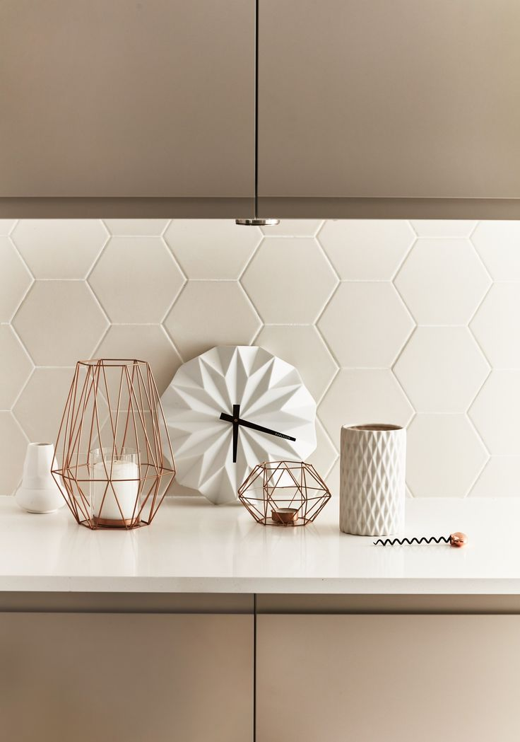 A minimal and considered use of statement decorative pieces in tones of copper and cream set against a backdrop of geometric tiles creates a clean yet styled environment. Clerkenwell Matt Cashmere from The Contemporary Collection by Howdens Joinery
