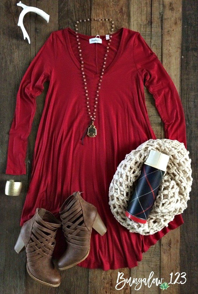 Ultra-comfortable T-shirt dress. Swing fit with a V-neck. Dress measures slightly shorter on the sides than the front. Shown with the Urban Booties, Free Bird Necklace, and Pierside Infinity Scarf in