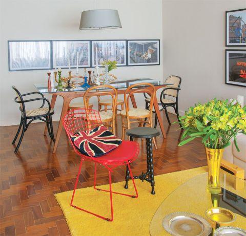 Cadeiras da Thonart e pendente da Lustres Yamamura. Na parede, fotos de viagens do morador. Ao lado da cadeira Bertoia vermelha, banco de brechó.