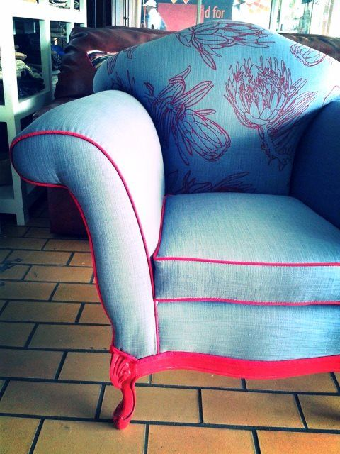 Vintage armchair: re-upholstered in denim and red print with red feet.