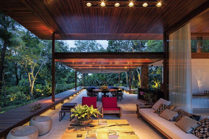 """A implantação em """"L"""" desta casa formada por 2 volumes interligados através da pérgula de entrada, protege o pátio e a piscina do visual da rua."""