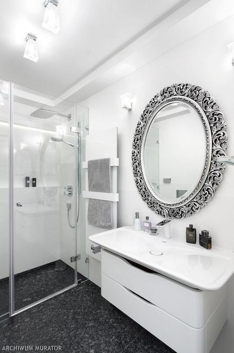 Biała łazienka z dekoracyjnym lustrem