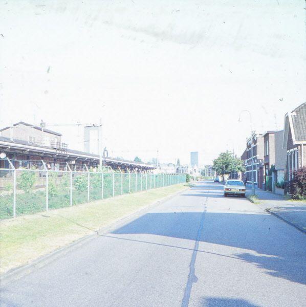 Almelo, De Parallelweg met het zicht op het station Almelo ter hoogte van huisnummer 50 direct aan de rechterzijde, met na het hoge blok met huizen, de afslag rechts naar de Appelstraat.