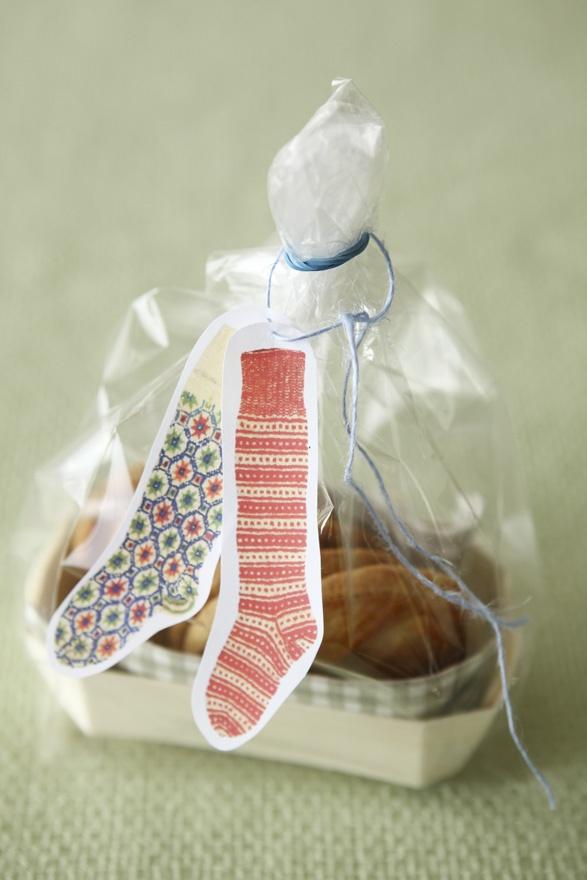 紙で作った飾りに刺繍糸を通し、透明の袋の口に結びます。/おいしいスイーツギフト(「はんど&はあと」2011年12月号)