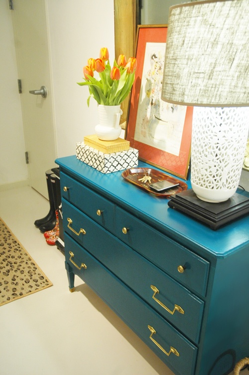 Colorful Small Entryway Idea - Refurbished dresser painted a blueberry blue, cut-out pottery lamp, contrasting colored frame to catch the eye, and substantially-framed mirror to make the space feel larger!