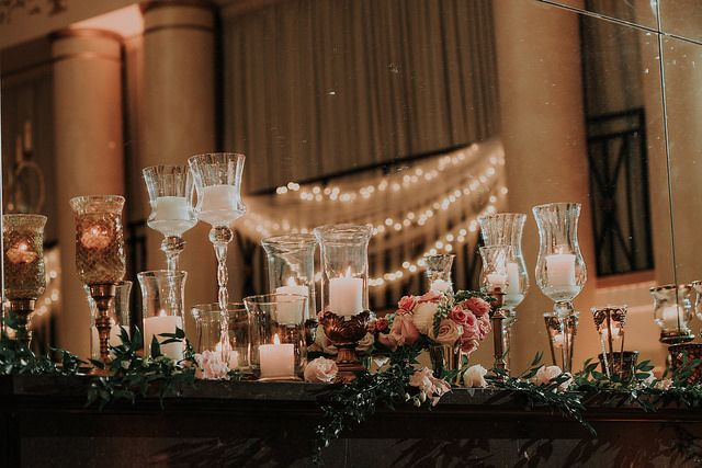 A glowing, luxe backdrop of elegant candlelight for Ashley and Patrick's head table on the fireplace at the DuPont Country Club. Kelli Wilke Photography.
