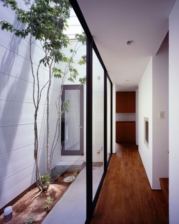 Located in Himeji Japan Adzuki House (2010) by Horibe Naoko Architect Office. The trees in the courtyard can be viewed from each room so you can sense the turn of the seasons indoors. The split-level floor and open ceiling combination let you enjoy altering open spaces with expansion in vertical and horizontal directions. Plaster walls and solid oak wooden floor are used to match their furniture #Japan #japanese #courtyard #light #lighting #detail #garden