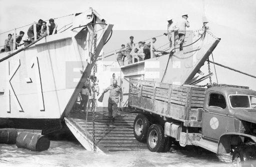 Guerra de Ifni.- Villa Bens (Cabo Juby), 10 de enero de 1958.- Los buques anfibios llegados a esta costa con mercancia son descargados rápidamente antes de que suba la marea. Oficiales y marinería trabajan de firme para que no se pierda un centímetro de terreno con la marejada.- EFE / jt