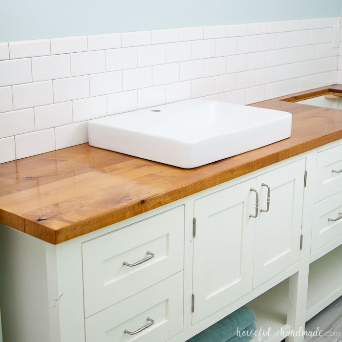 Add rustic warmth to your farmhouse bathroom by adding a waterproof wood vanity top. Learn how to build & protect a wood vanity top for your DIY renovation.