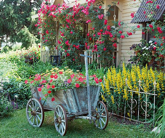 successful mix of container plants and overflowing beds. We were enchanted by the antique goat cart that doubles as an eye-catching centerpiece and a unique planter for 'Red Wave' petunias and yellow African daisies. Next to the cart, lysimachia adds brilliant color behind a weathered iron fence. Test Garden Tip: Recreate this look by mixing antique garden accessories with a salvaged section of fence or edging (or even an old metal headboard for a bed).