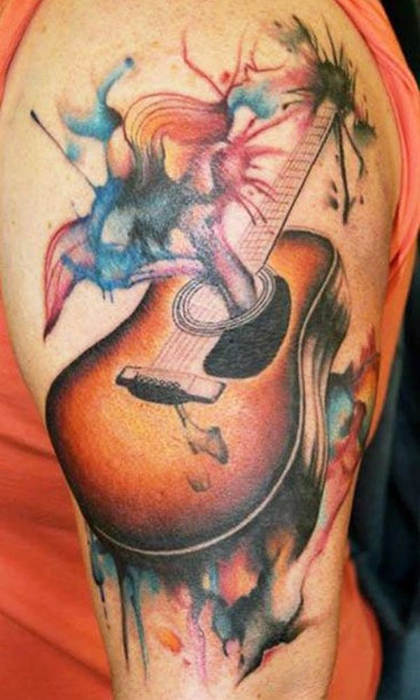 Acoustic guitar tattoo on the arm. The guitar is shown to be producing a splash of various colors. It's like seeing an explosion of music in form of colors.