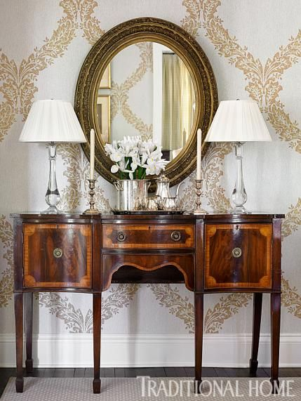 An antique sideboard and oval mirror pump up the glam in this dining room.  - Traditional Home ® / Photo: Emily Jenkins Followill / Design: Lauren DeLoach
