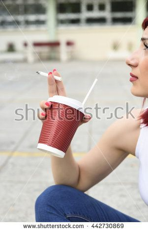Beautiful young redhead woman holding cigarette and a cup of coffee