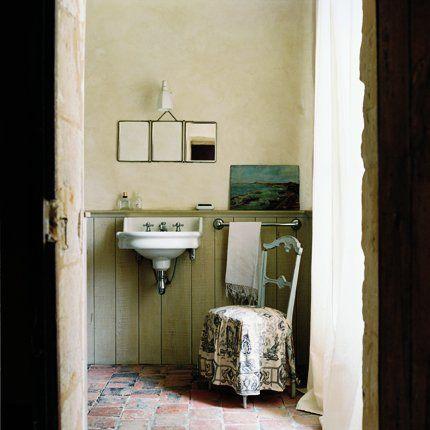 Salle de bain ancienne joliment nostalgique avec chaise chinée et petit lavabo blanc