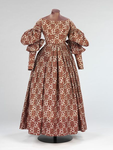 (1836-1838) Wool was a popular fabric for winter day wear, as seen in this example. The dress is printed in a complicated design of shamrocks on a lilac and brown chequered ground. By the mid-1830s the puff of the full gigot sleeve was moving from the top of the arm to the elbow.
