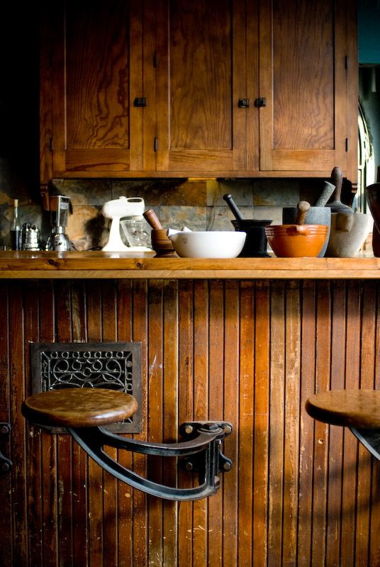 awesome bar stool idea. i think its on a pivot hinge as well to allow easy off/on access. Nice wood in kitchen as well.