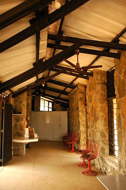 Gobhai Mountain Lodge: Lonavala Interior view of the living space finished in a plain cement flooring. Random rubble masonry with a timber truss and corrugated asbestos roofing sheets form the superstructure of the lodge   Archnet
