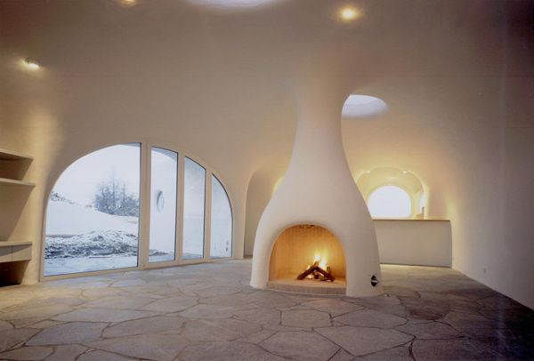 Earth House Estate Pallavincini located in Arni, Switzerland. An inside view of the fireplace and door to the outside.