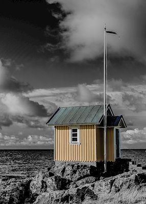 Stefan Kjellerup - Baduset i Torekov. Partially black and white photography of a small cabin by the sea. Available as poster and laminated picture at Printler, the marketplace for photo art.
