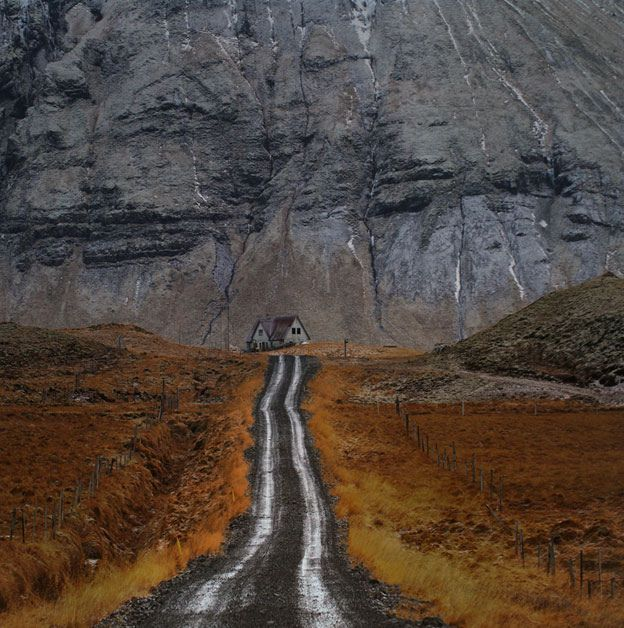 Believed to be Iceland. I love that (relatively) little house under that towering cliff and the way the road leads the eye directly to the house.