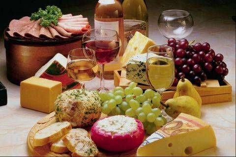 This cheese platter features Swiss cheese, a cheese ball, blue cheese (or roquefort), Parmesan and cheddar cheeses. There is also a cottage cheese dip along with a platter of cold-cuts (probably slices of ham and roast beef) as well as grapes. To drink, there are glasses of white and rose wine.