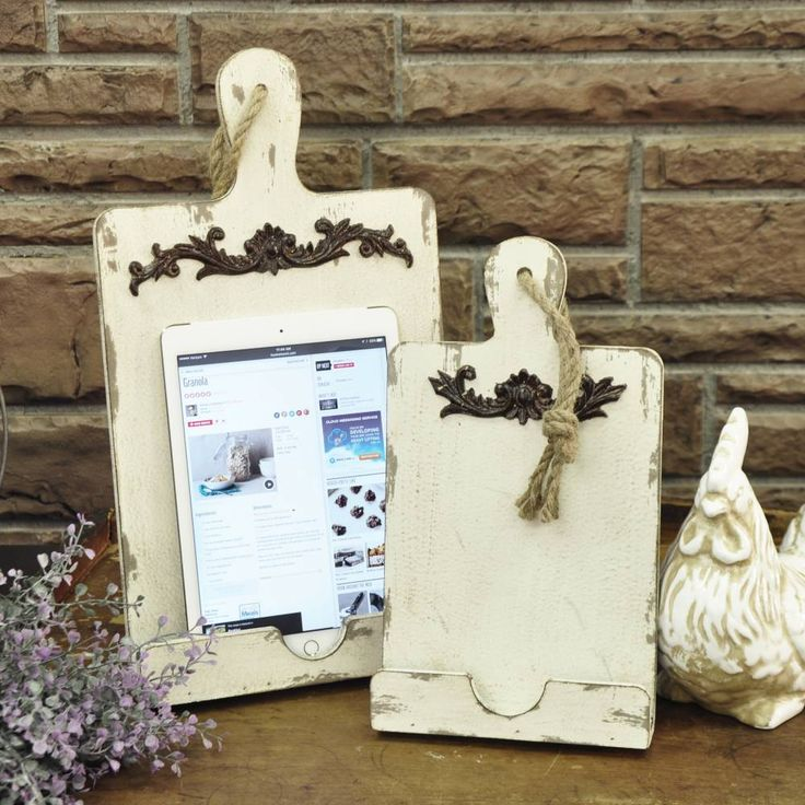 "Modern and vintage join together in this mock cutting board that holds an iPad Mini or tablet for easy recipe viewing. Oh, of course, it also holds a smaller traditional cookbook! Hinged back support allows the Tablet/Cookbook Holder to be free standing. The time-worn distressed vintage cream finish is perfect for a country or farmhouse kitchen. 12.5"" high x 7"" wide. Shown on right."