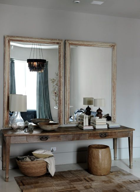 pair of antique mirrors hangs over a vintage farm table in the dressing area at the apt of Harriet Maxwell and Andrew Corrie of Ochre in NYC