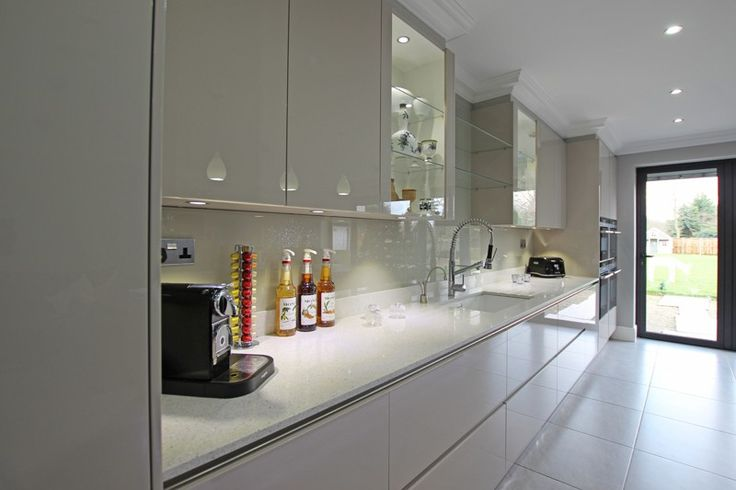 Gloss cashmere handle-less units, wide pan drawers, pale floor and glass wall units mixed in