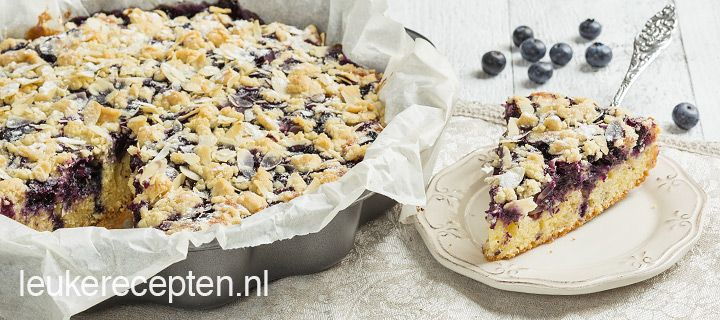 Luchtige cake van yoghurt met frisse blauwe bessen en een krokante amandelcrumble laag