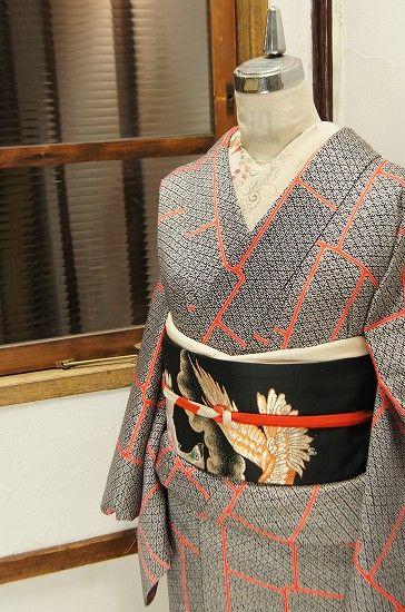黒地に凛と映える白で染め出された花菱を、鮮やかな朱色が繋ぎ合わせた幾何学模様がモダンな正絹綸子の袷着物です。