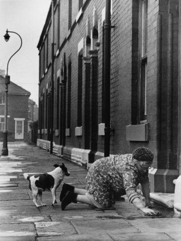 © Shirley Baker  Elderly Lady Washing Her Step - Manchester 1968