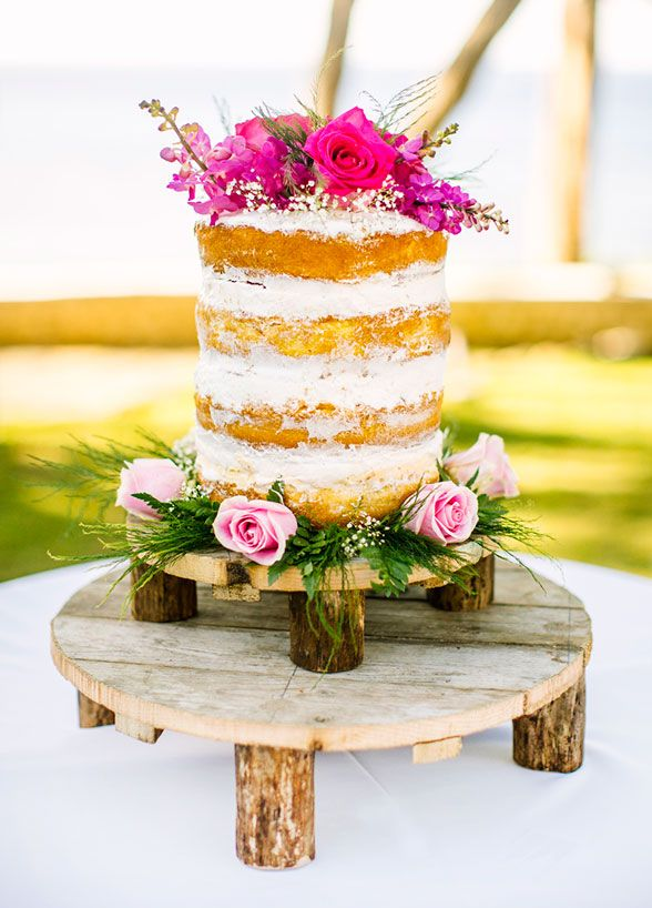 A simple chic naked wedding cake decorated with fresh flowers.