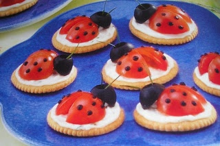 "Ladybug Appetizers  2 oz cream cheese, softened  2 Tbsp. sour cream  1/2 tsp. snipped chives  1/8 tsp. minced parsley  1/8 tsp. garlic salt  Black paste food coloring  36 butter-flavored crackers  18 cherry tomatoes, quartered  18 large pitted ripe olives  72 fresh chive pieces (about 1 1/2"" long)"