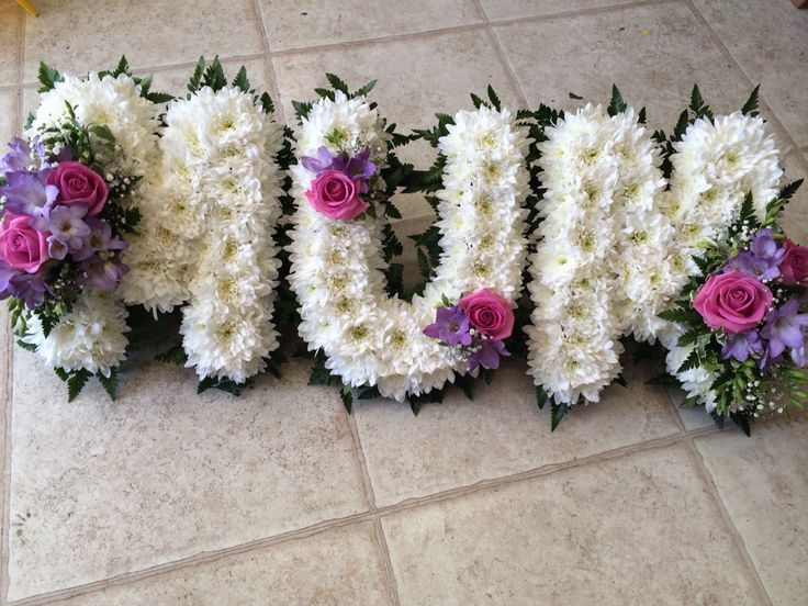 MUM letters funeral flowers based design foliage edge pink and lilac sprays pink roses lilac freesias by Lily White florist West Midlands