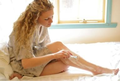 Pretty Blonde Woman Shaving Legs - Fotosearch/Getty Images