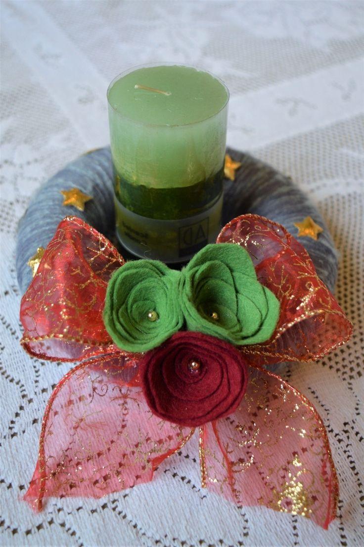 Svícen+s+růžemi+Svícen+má+polystyrenový+základ+a+je+omotaný+modro+šedou+bavlnkou.+Hodí+se+na+vánoční+stůl+kde+se+udržuje+vánoční+klasika+červených+a+zelených+barev.+Plstěné+růžičky+doplňuje+červeno+-+zlatá+sváteční+stuha+s+mašlí.+Věneček+svícnu+se+hodí+na+průměr+svíce+do+6,5cm.+Zde+je+použita+zelená+svíčka+o+průměru+4,5cm.