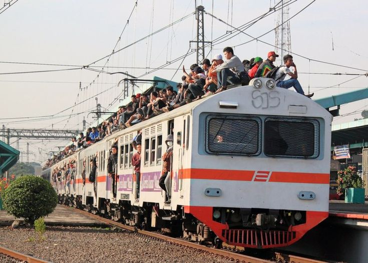 A crowded KRL Jabotabek electric multiple-unit train with passengers riding on the outside in Jakarta, Indonesia