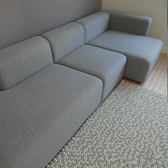 """Et rektangulært håndlaget teppe i moderne farger: lysgrått med hvitt. Produsert i 100% ull, helt fritt for skadelige stoffer. Kuleteppet """"Andrea"""" leveres på spesialbestilling. Leveringstid er normalt ca 3 måneder."""