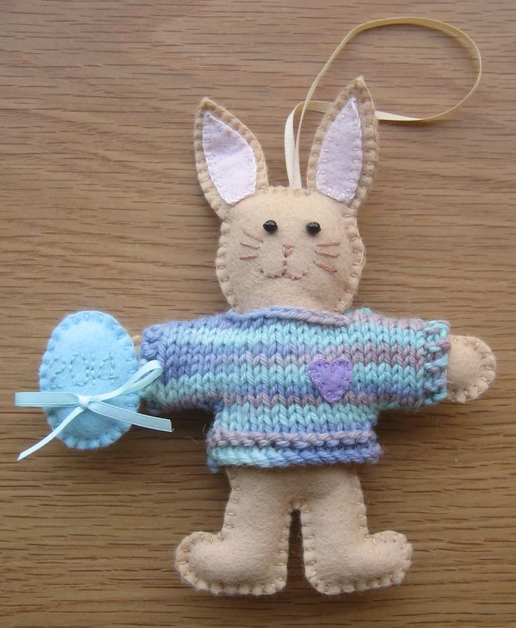This felt bunny makes a lovely Easter gift.  Stitched from honey coloured felt he wears a hand knitted jumper and carries an egg embroidered with the year.  Perfect for baby's first Easter.  Orders now being taken for 2015.  Other colours available.