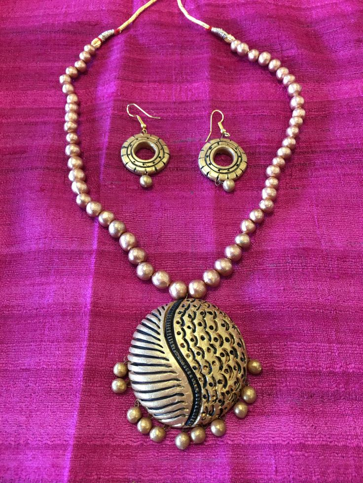 - This simple but elegant clay set is handcrafted and baked to set to go seamlessly with formal or casual attire. The pendant is hand-stamped with intricate design on clay and painted with glossy meta