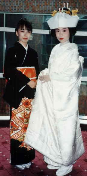 A picture of two sisters. On the left wearing a tomesode kimono at her sister's wedding (right) wearing a Uchikake - the wedding kimono
